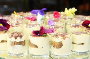 Custard desserts in glass holders decorated with flowers