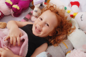 Ruby lying amongst soft toys family photography