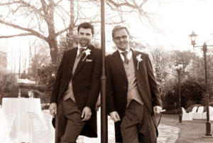 Bridegroom and bestman lean on lamp post