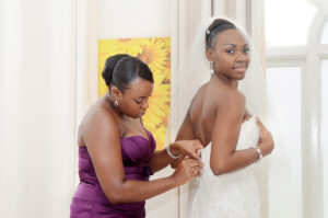Bridesmaid helps bride dress