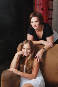 Mom leaning over chair with seated daughter