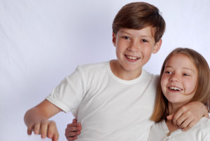 Two white children with arms round each other -family studio photography