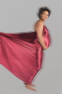 Pregnant full length woman in red satin