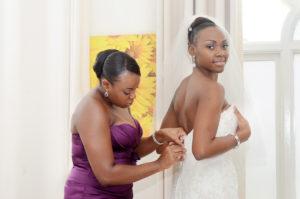 Bridesmaid helps bride dress